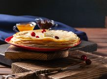 English-style pancakes with berries, traditional for Shrove Tuesday. Traditional classic thin golden flapjack on the plate and. Napkin on the wooden background stock photo