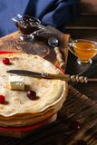 English-style pancakes with berries, traditional for Shrove Tuesday. Traditional classic thin golden flapjack on the plate and. Napkin on the wooden background stock photography