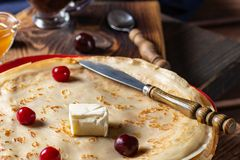 English-style pancakes with berries, traditional for Shrove Tuesday. Traditional classic thin golden flapjack on the plate and. Napkin on the wooden background royalty free stock image