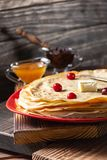 English-style pancakes with berries, traditional for Shrove Tuesday. Traditional classic thin golden flapjack on the plate and. Napkin on the wooden background royalty free stock photo
