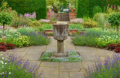 English summer garden. Flagged garden with ornamental vase and various flowers royalty free stock images