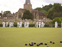 English summer village bowling green. Quintessentially english past time of green bowling in english sleepy village, set against church and graveyard royalty free stock image