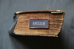 English, tag with the text written in it and book. English tag and vintage book On the school board Stock Photography