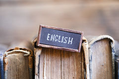 English, tag with the text written in it and books. English tag and vintage books on a bookshelf Royalty Free Stock Photo