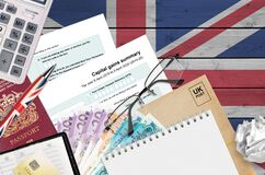 English Tax form sa107 Capital gains summary from HM revenue and customs lies on table with office items. HMRC paperwork and tax