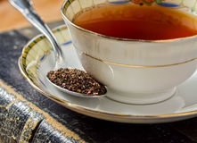 English Tea. A freshly brewed cup of tea in an antique cup with dried tea leaves royalty free stock image