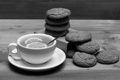 English tea and bakery concept. Oatmeal biscuits as tasty pastry for cup of tea. With lemon and honey. Cookies on carton box near tea on grey wooden background Royalty Free Stock Image