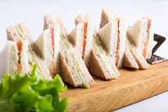 English tea sandwiches platter on wooden board. Over light background Royalty Free Stock Photography