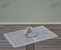 English teacup and saucer with floral decor and silver rim, on a sheet of music royalty free stock photo