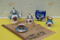 English tea set, a package of original English Tetley`s teabags and reading glasses on an old German daily newspaper Der Patriot stock image