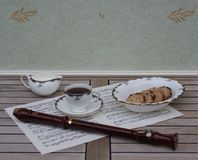 English teacup with saucer, cream jug and a cake bowl, fine bone china porcelain, and a block flute on a sheet of music royalty free stock photos