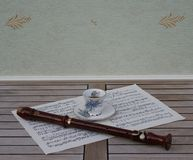 English teacup and saucer with floral decor and silver rim and a block flute on a sheet of music stock photography