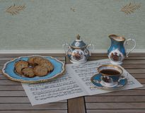 English teacup with saucer, sugar bowl, cream jug and a cake plate with cookies, fine bone china porcelain, on a sheet of music royalty free stock image