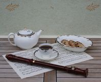 English teacup with saucer, teapot and a cake bowl, fine bone china porcelain, and a block flute on a sheet of music royalty free stock photography