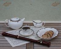 English teacup with saucer, teapot, cream jug and a cake bowl, fine bone china porcelain, and a block flute on a sheet of music. English fine bone china royalty free stock image