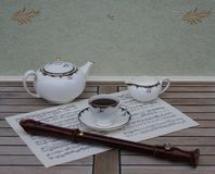 English teacup with saucer, teapot and cream jug, fine bone china porcelain, and a block flute on a sheet of music stock image