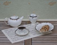 English teacup with saucer, teapot, sugar bowl and a cake bowl with cookies, fine bone china porcelain, on a sheet of music royalty free stock photo