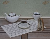 English teacup with saucer, teapot and sugar bowl, fine bone china porcelain, and a metronome for music on a sheet of music. English fine bone china Porcelain royalty free stock photography