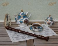 English teacup with saucer, teapot and sugar bowl, metronome for music and a block flute on a sheet of music royalty free stock photos