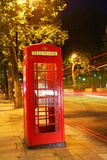 English telephone booth in the night with traffic light trails Royalty Free Stock Photo
