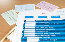 English test and answer sheet. Blue english verb test on table Stock Image