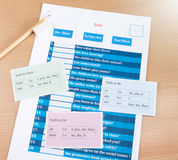 English test and answer sheet. Blue english verb test on table Stock Photography