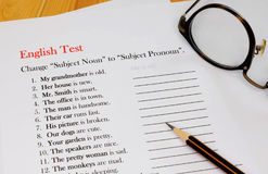 English test sheet on wooden desk. Represent school test in classroom Royalty Free Stock Photography