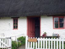 English thatched white cottage. PIcturesque English white thatched cottage in countryside Stock Photography