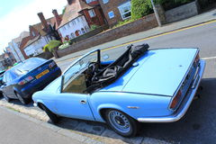 English retro car. Traditional old car and nice houses at the background on a street in Deal,Kent,England.The Triumph Spitfire is a small English two-seat sports Royalty Free Stock Images
