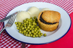 English traditional pie with mashed potatoes and garden green peas with gravy on the red table Stock Photo