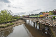 English train on traveling on bridge over a river Stock Image