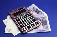 English Twenty Pound notes with calculator. Two English Bank of England Twenty Pound notes on blue background, with pink bling calculator Royalty Free Stock Photos