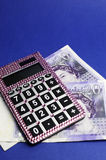 English Twenty Pound notes with calculator. Vertical. Two English Bank of England Twenty Pound notes on blue background, with pink bling calculator. Vertical Stock Photos