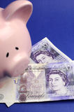 English twenty pound notes with piggy bank - vertical. Two English Bank of England Twenty Pound notes on blue background with pink piggy bank for savings and Royalty Free Stock Images
