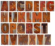 Alphabet set in vintage wood type. English uppercase alphabet set - a collage of 26 isolated antique wood letterpress printing blocks with a digital painting royalty free stock photos