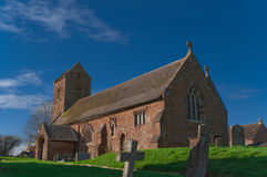 English Village Church. Ancient English Village Church and Graveyard agianst a Blue Sky Stock Image