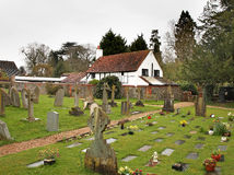 English Village Churchyard and Cottage. An English Village Churchyard with Timber Framed Cottage in the background Royalty Free Stock Photo