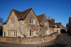 English Village corner house Laycock UK. Traditional old fashioned English stone corner house in the famous English village of Laycock Wiltshire UK Stock Photos