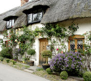 English Village Cottage. Thatched flower strewn English Village Cottage Royalty Free Stock Photography
