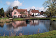 English village pond. On village green with small shops and houses reflected in water Stock Image