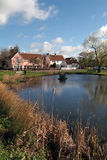 English village pond. On village green with small shops and houses reflected in water Stock Images