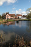 English village pond. On village green with small shops and houses reflected in water Royalty Free Stock Images