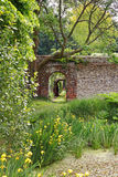 An English Walled Garden. Archway into an English Walled garden with irises around a pond Stock Photography