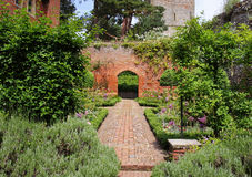 An English Walled Garden with arch. A Formal english Walled garden with path leading to an Arch through a brick wall Stock Photo