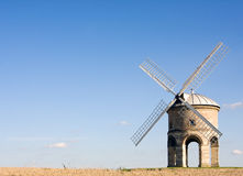 English windmill in summer with blue skies. The famous listed windmill at Chesterton in Warwickshire, England, on a sunny summer afternoon. Wheat field in the Royalty Free Stock Image