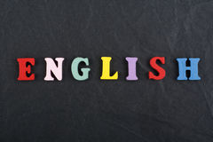 English word on black board background composed from colorful abc alphabet block wooden letters, copy space for ad text stock image