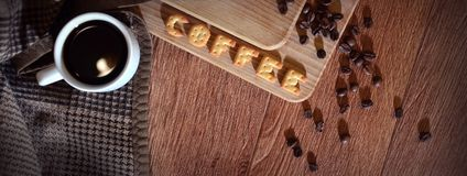English word & x22;Coffee& x22;, made up of salt cracker letters. Still life with a small white cup of hot coffee and a salt cracker in the form of letters royalty free stock images