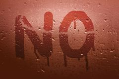 The English word No. Is written with a finger on the surface of the misted glass royalty free stock images
