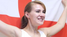 English Young Woman Celebrates holding the Flag of England in Slow Motion. High quality stock image