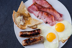 Englsih breakfast with bacon, pork and apple sausages Stock Image